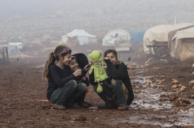 Children play with a doll in the mud at Abu Fida refugee camp in Idlib, Syria on January 6, 2021. (Photo by Ahmet Karaahmet/Anadolu Agency via Getty Images)