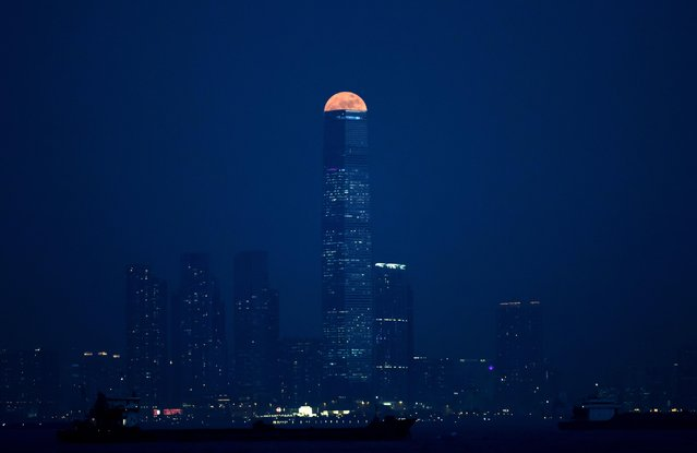 The moon rises over Victoria Harbour in Hong Kong, Monday, November 14, 2016. The brightest moon in almost 69 years lights up the sky this week in a treat for star watchers around the globe. The phenomenon is known as the supermoon. The tall building is the International Commerce Centre. (Photo by Kin Cheung/AP Photo)
