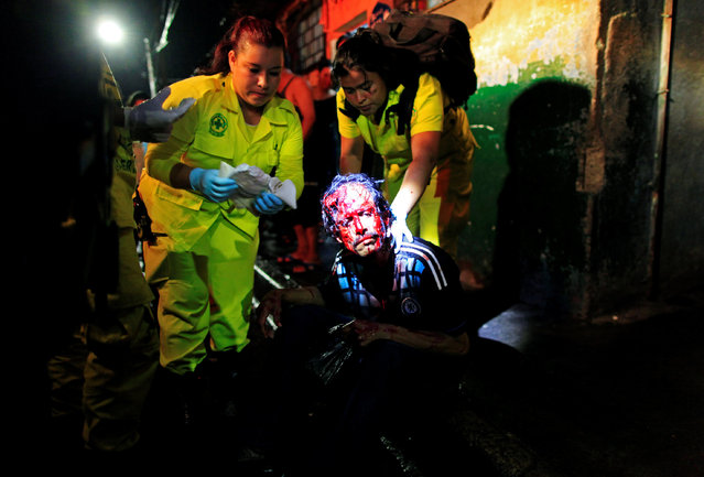 Comandos de Salvamento rescuers Maria Martinez (L) and Ana Chichilla attend to a wounded homeless man in San Salvador, El Salvador July 16, 2016. The man was attacked with a machete by suspected gang members. (Photo by Jose Cabezas/Reuters)