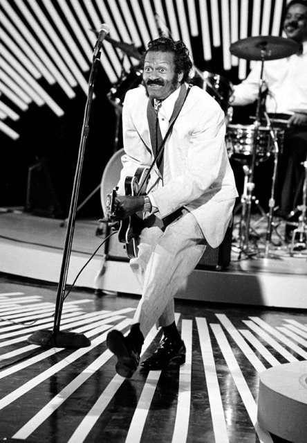 """American guitarist and singer Chuck Berry performs his """"duck walk"""" on stage as he plays his guitar on April 4, 1980. The location is not known. (Photo by AP Photo)"""