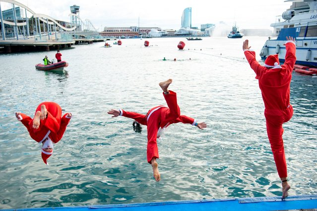Participants sporting Santa Claus costumes jump into the water during the 111th edition of the Copa Nadal (Christmas Cup) swimming race in Barcelona's Port Vell on December 25, 2020. The traditional 200-meter Christmas swimming race gathered around 300 participants on Barcelona's Port Vell (old harbour). (Photo by Josep Lago/AFP Photo)