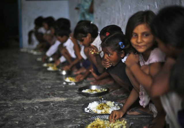 School children eat their free mid-day meal, distributed by a government-run primary school, at Brahimpur village in Chapra district of the eastern Indian state of Bihar July 19, 2013. Police suspect that India's worst outbreak of mass food poisoning in years was caused by cooking oil that had been kept in a container previously used to store pesticide, the magistrate overseeing the investigation said on Friday. (Photo by Adnan Abidi/Reuters)
