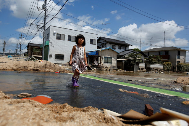 A local resident walks in a flood affected area in Mabi town in Kurashiki, Okayama Prefecture, Japan on July 10, 2018. (Photo by Issei Kato/Reuters)