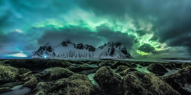 The magical Aurora Borealis explodes from the clouds and looms over the mountains in Stokknes on the south coast of Iceland. (Photo by Jingyi Zhang/Astronomy Photographer of the Year 2018)