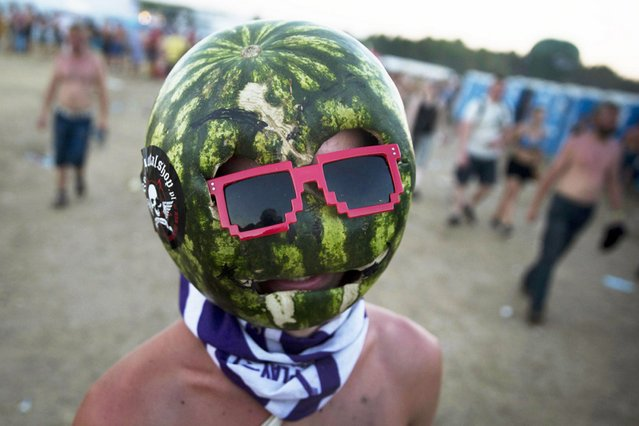 Watermelon Man: A man wears a mask at the Woodstock Festival in Kostrzyn-upon-Odra River, close to the Polish-German border, on August 3, 2013. (Photo by Thomas Peter/Reuters)