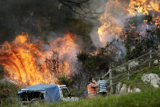 Two neighbors look at the flames as firefighters work to extinguish a forest fire at Ribera de Arriba in Asturias, Spain, 28 December 2015. Up to 49 forest fires are still active in Asturias. (Photo by Alberto Morante/EPA)