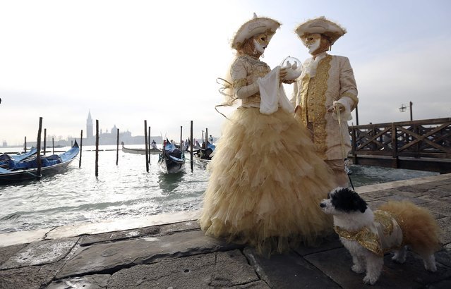 Masked revellers pose in front of St. Mark square during carnival in Venice, February 8, 2015. (Photo by Stefano Rellandini/Reuters)