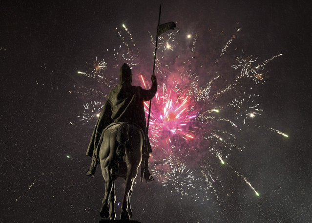 Fireworks light the sky above the Statue of St. Wenceslas at Prague's Wenceslas Square during the New Year celebrations in Prague, Czech Republic, Friday, January 1, 2016. (Photo by Katerina Sulova/CTK via AP Photo)