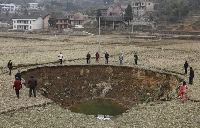 People stand by a recent caved-in area on a paddy field in Fukou county, Hunan province, January 12, 2013. More than 20 pits formed from the sunken ground surface in Fukou county during the past four months. According to the local media, the government's initial investigation showed years of mining destroyed the local underground water systems and led to the numerous cave-ins. (Photo by Reuters/China Daily)