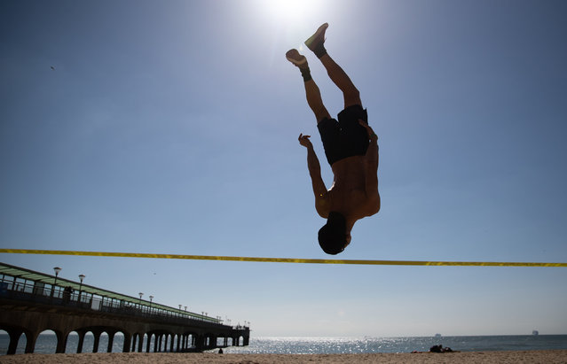 A slackliner practices his skills on Boscombe beach in Dorset, United Kingdom on Friday, April 2, 2021. (Photo by Andrew Matthews/PA Images via Getty Images)