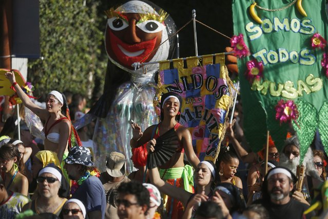 """Revellers take part in an annual block party known as """"Carmelitas"""", one of the many carnival parties to take place in the neighbourhoods of Rio de Janeiro February 13, 2015. (Photo by Pilar Olivares/Reuters)"""