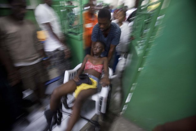 A reveler who was injured during carnival celebrations waits for treatment at the emergency room of the General Hospital in Port-au-Prince, Haiti, early Tuesday, February 17, 2015. At least 20 people on a music group's packed Carnival float in the Haitian capital were killed Tuesday when they were electrocuted by a power line, officials said. (Photo by Dieu Nalio Chery/AP Photo)