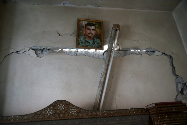 A picture is hung on a damaged wall in a site hit by what activists said were airstrikes carried out by the Russian air force in the town of Douma, eastern Ghouta in Damascus, Syria January 10, 2016. (Photo by Bassam Khabieh/Reuters)