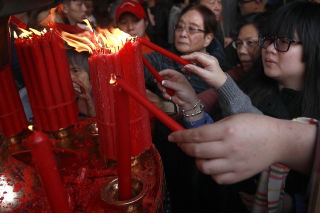 Devotees light candles during Chinese Lunar New Year celebrations at the Lungshan temple in Taipei February 19, 2015. (Photo by Pichi Chuang/Reuters)