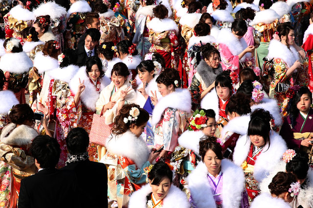 Men and women dressed in Kimono and suits attend the Coming of Age Day ceremony outside of Noevir Stadium on January 11, 2016 in Kobe, Japan. The Coming of Age Day is a Japanese national holiday to congratulate and encourage those who have reached the age 20. The Statistics Bureau of Japan announced last month the number of people aged 20 years old, the legal age of adulthood in Japan, reached a record-equal low of 1.21 million, down 50,000 from the previous year. (Photo by Buddhika Weerasinghe/Getty Images)