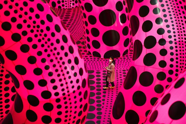 """A woman walks through the art work """"A Bouquet of Love I Saw in the Universe"""" by Yayoi Kusama during the press preview of a retrospective exhibition of the Japanese artist at the Martin Gropius Bau museum in Berlin, Germany, Thursday, April 22, 2021. The exhibition will run from April 23 to August 15, 2021. (Photo by Markus Schreiber/AP Photo)"""