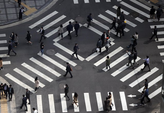 Pedestrians walk at a crossroads in Seoul, South Korea, 26 March 2021. The South Korean government announced on 26 March an extension of the ongoing COVID-19 restriction that were originally set to end on 28 March. The restrictions, enforced for two more weeks, include a ban on meetings of five people or more. (Photo by Yonhap/EPA/EFE)