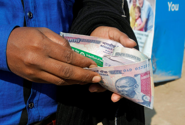 A man puts his debit card inside an Indian currency printed wallet outside a bank in Agartala, India November 28, 2016. (Photo by Jayanta Dey/Reuters)