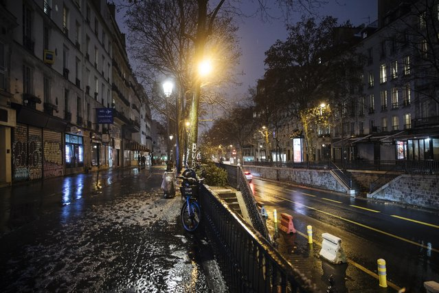 An empty street as the 6 p.m curfew starts in Paris, Saturday January 16, 2021. The prime minister announced Thursday an extension of the 6 p.m.-to-6 a.m. curfew to cover the whole country, including zones, like Paris, where it previously hadn't started until 8 p.m. Shopping and all outdoor leisure activities stop at curfew, only short pet walks allowed. Working and commuting allowed with note from employer. Food deliveries but not takeout allowed. Fines for curfew-breakers. (Photo by Lewis Joly/AP Photo)