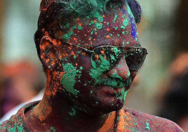 An Indian youth is covered with coloured powder during Holi celebrations in Mumbai on March 6, 2015.  Holi, the festival of colours, is a riotous celebration of the coming of spring and falls on the day after full moon annually in March. Revellers spray coloured powder and water on each other with great gusto, whilst adults extend the hand of peace.  AFP PHOTO / PUNIT PARANJPE        (PUNIT PARANJPE/AFP/Getty Images)