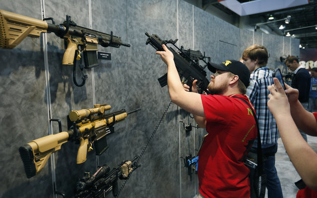 Nolan Hammer looks at a gun at the Heckler & Koch booth at the Shooting, Hunting and Outdoor Trade Show, Tuesday, January 19, 2016, in Las Vegas. (Photo by John Locher/AP Photo)