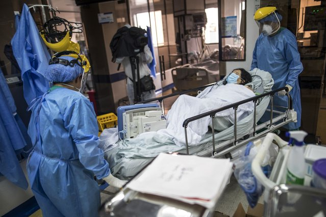 Healthcare workers move a COVID-19 patient, inside an ICU of the Samaritana Hospital in Bogota, Colombia, Thursday, June 3, 2021. Colombia has become a pandemic hotspot experiencing a third wave of COVID-19 infections and a surge in deaths. (Photo by Ivan Valencia/AP Photo)