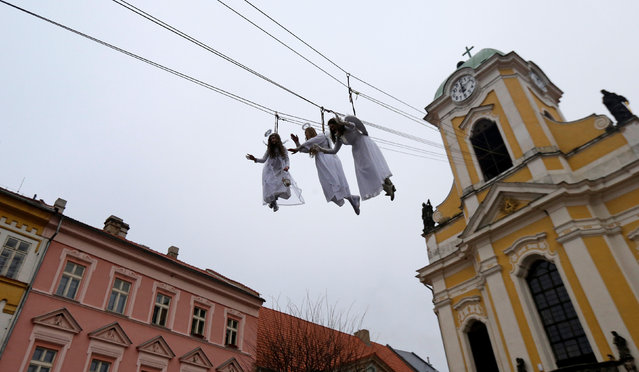 Women dressed as angels wave to spectators as they hang from a wire during a Christmas market in the town of Ustek, Czech Republic December 17, 2016. (Photo by David W. Cerny/Reuters)