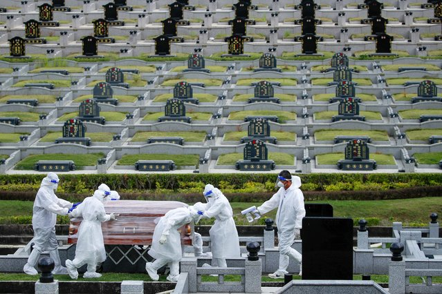 People in protective suits carry a coffin of a person who died with COVID-19 at a graveyard in Setia Alam, outside Kuala Lumpur, Malaysia, 08 June 2021. According to Health director-general Noor Hisham the total COVID-19 cases recorded in Malaysia till 08 June is 627,652 cases. (Photo by Fazry Ismail/EPA/EFE)