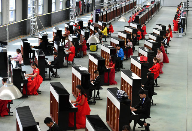 Participants play pianos together to set a Guinness World Record for the most pianos played at the same time at Wuqiang County on October 6, 2018 in Hengshui, Hebei Province of China. 666 pianos were played together in the challenge in Hengshui on Saturday. (Photo by Zhai Yujia/China News Service/VCG via Getty Images)