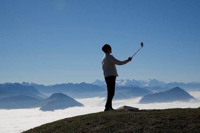 A man takes a picture with his smartphone mounted on a selfie stick during sunny autumn weather near the peak of Mount Rigi, Switzerland on October 22, 2018. (Photo by Arnd Wiegmann/Reuters)