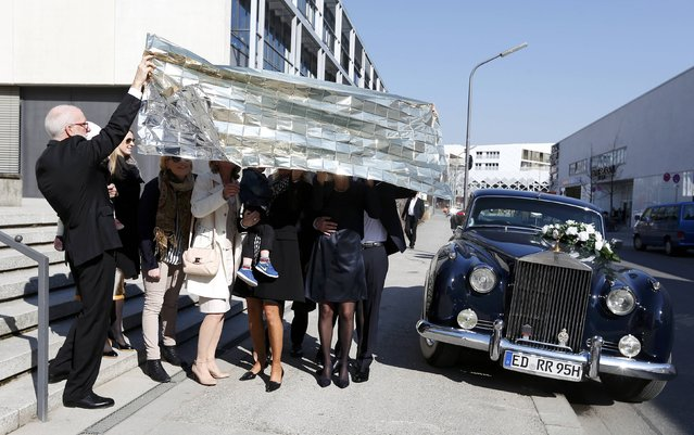 Bridal pair Sarah Wolf and Michael Wilde (R) and their guests look through a rescue foil as they watch a partial solar eclipse in Munich March 20, 2015. (Photo by Michaela Rehle/Reuters)