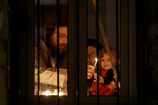 An ultra-orthodox Jewish family lights a candle on the first night of the holiday of Hanukkah in Jerusalem's Mea Shearim neighbourhood December 24, 2016. (Photo by Amir Cohen/Reuters)