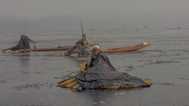 Kashmiri fishermen holding harpoons, covered under blankets, wait in their boats to catch fish in the partially frozen Anchar lake on December 28, 2016 in Srinagar, the summer capital of Indian administered Kashmir, India. (Photo by Yawar Nazir/Nur Photo)