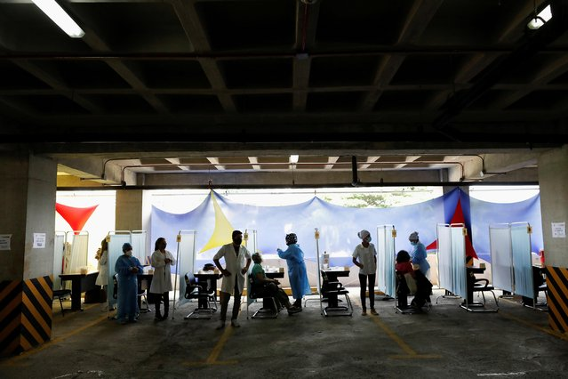 People receive their first dose of Russia's Sputnik V coronavirus vaccine in the parking lot of the Social Security Institute of the Armed Forces, turned into a mass vaccination centre, in Caracas, Venezuela on June 5, 2021. (Photo by Leonardo Fernandez Viloria/Reuters)