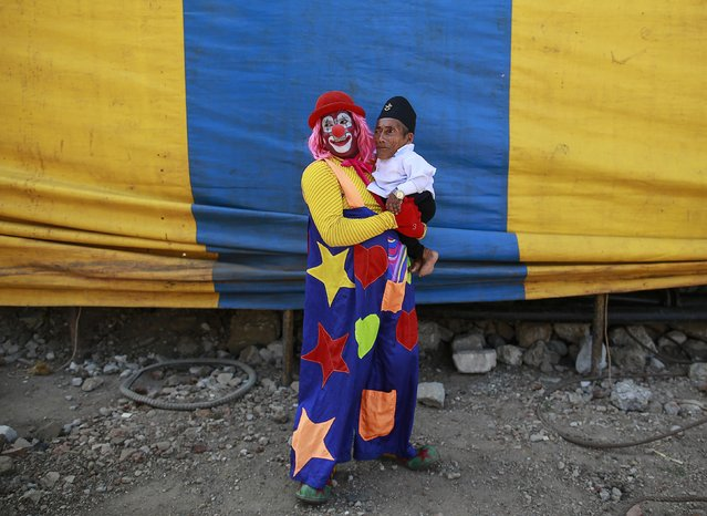 The world's shortest man Chandra Bahadur Dangi, 72, is carried by a clown after an event at the Rambo Circus in Mumbai March 18, 2015. Dangi, who is from Nepal and stands at 54.6cm (21.5 in), stopped over in India on his way to the South Pacific island of Samoa to make a guest appearance in a circus. (Photo by Danish Siddiqui/Reuters)