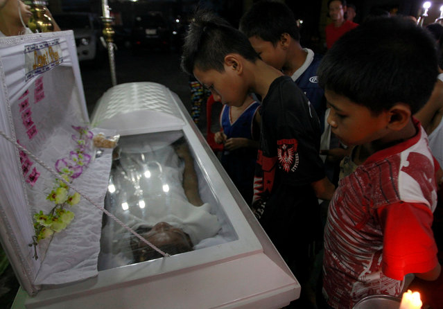 Grieving relatives and friends attend the wake of Kristine Santor, 44,  who according to police was killed by unidentified gunmen at a drug den, in Caloocan city, Metro Manila, Philippines December 30, 2016. (Photo by Czar Dancel/Reuters)