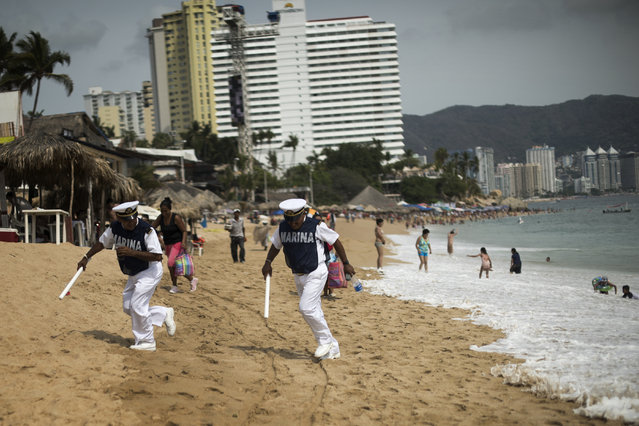 Mexican Marines patrolling the beach run to avoid a wave on April 2, 2015 in Acapulco, Mexico. (Photo by Jonathan Levinson/The Washington Post)