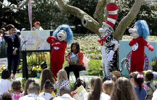 """U.S. First lady Michelle Obama (C) reads """"Oh, the Things You Can Do That Are Good For You"""", a Tish Rabe adaptation of a Dr. Seuss book, to children visiting the White House during the annual Easter Egg Roll in Washington April 6, 2015. At left is Genevieve Goings from the Disney Channel. (Photo by Gary Cameron/Reuters)"""