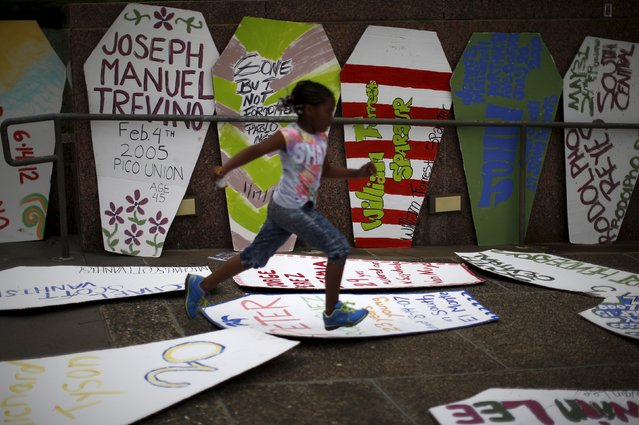 A girl runs past coffins to commemorate the more than 617 people they say have been killed by law enforcement in LA County since 2000, in Los Angeles, California April 7, 2015. (Photo by Lucy Nicholson/Reuters)