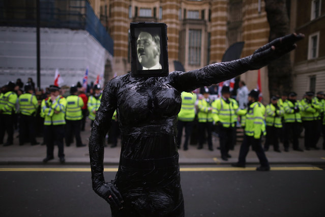 A man dressed in black with an image of Adolf Hitler on his face stands in front of Pegida Rally as it takes place on Whitehall on April 4, 2015 in London, England. The British offshoot of the German anti islamisation group Pegida, were met by anti fascist protesters as they held their first protest in London today. (Photo by Dan Kitwood/Getty Images)