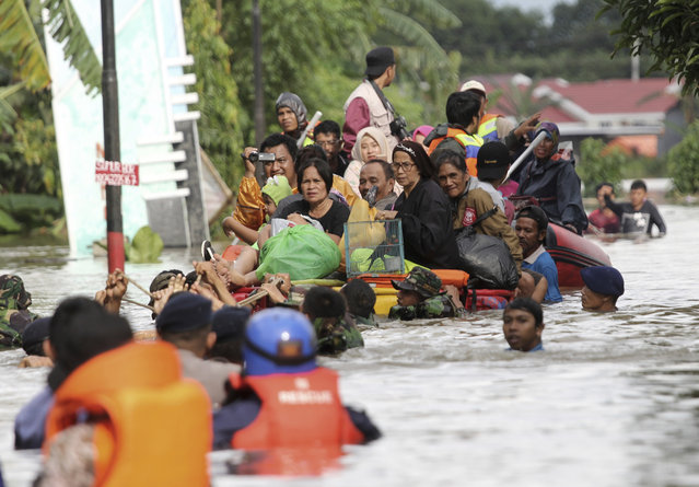 Residents ride a makeshift raft as they evacuate their flooded homes in Makassar, South Sulawesi, Indonesia, Wednesday, January 23, 2019. Torrential rains that overwhelmed a dam and caused landslides that killed some and displaced more than a few thousand residents in central Indonesia, officials said Wednesday. (Photo by Masyudi Syachban Firmansyah/AP Photo)