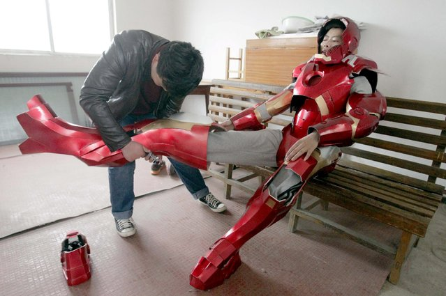 Cheng Chen (L), a 27-year-old worker at a state-owned enterprise, helps his nephew to put on his home-made Iron Man armour in Xuzhou, Jiangsu province April 13, 2015. It cost Cheng about 500 yuan ($81 USD) to make the armour, which weighs about 4 kilograms, with plastic boards and LED lights, local media reported. (Photo by Reuters/Stringer)