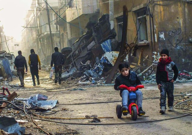 A boy rides on a tricycle along a damaged street in the besieged area of Homs, Syria, on January 1, 2013. (Photo by Yazan Homsy/Reuters)