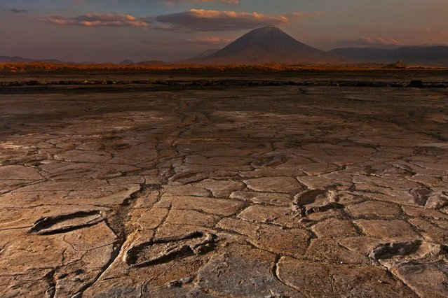 To celebrate the 125th anniversary of the National Geographic Society, the October issue of National Geographic focused on discoveries through photography. This portrait shows footprints in volcanic ash at Engare Sero in Tanzania – believed to belong to a fast-moving party of adults and adolescents in the Pleistocene era, more than 10,000 years ago. The footprints provide evidence of modern humans moving through East Africa. (Photo by Robert Clark/National Geographic)