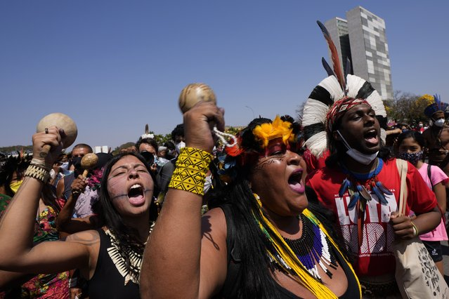 """Indigenous protesters shout """"Get out Bolsonaro"""", referring to President Jair Bolsonaro, outside Planalto presidential palace in Brasilia, Brazil, Friday, August 27, 2021. Indigenous are demanding the Supreme Court protect their land rights and reserves, asking justices to uphold their territorial rights in a landmark case that could open their lands to outside development by commercial interests. (Photo by Eraldo Peres/AP Photo)"""
