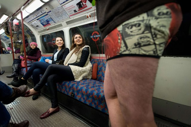 """Participants in the13th annual International """"No Pants Subway Ride"""" travel on a London underground train in London, on January 12, 2014. (Photo by Leon Neal/AFP Photo)"""