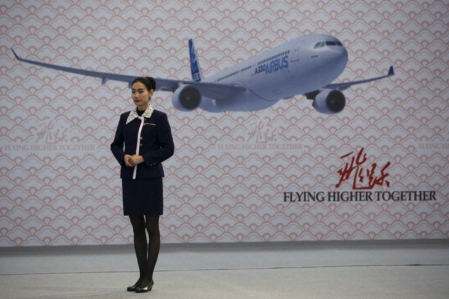 A staff member stands in front of an image of the Airbus A330 at a ground-breaking ceremony for the Airbus A330 completion and delivery center in Tianjin, China, March 2, 2016. (Photo by Kim Kyung-Hoon/Reuters)