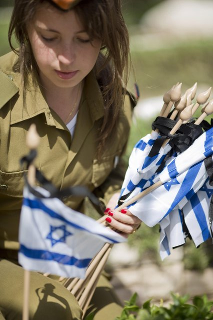 An Israeli soldier places a small national flag with a black ribbon on the grave of a fallen soldier on the eve of Memorial Day at the Kiryat Shaul military cemetery in Tel Aviv, Israel, Tuesday, April 21, 2015. Israel marks the annual Memorial Day in remembrance of soldiers who died in the nation's conflicts, beginning at dusk Tuesday until Wednesday evening. (Photo by Ariel Schalit/AP Photo)