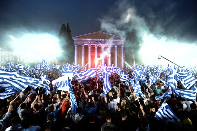 Supporters of Leader of the Greek conservative party New Democracy Antonis Samaras wave flags during a pre-election speech in Athens on May 3, 2012. (Photo by Aris Messinis/AFP Photo)
