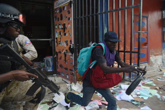 Haitian Police try to arrest a man who was caught looting a shop in the centre of Haitian Capital Port-au-Prince on February 12, 2019, as a sixth day of protests against Haitian President Jovenel Moise and the misuse of Petrocaribe funds continued. (Photo by Héctor Retamal/AFP Photo)